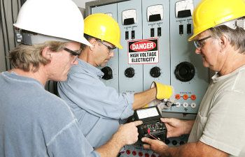 group of electricians using an ohm meter to test voltage